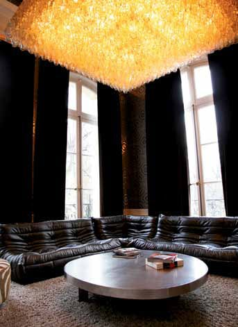 Kravitz's Paris sitting room features Highway 66 wallpaper from Flavor Paper; a Venini glass chandelier originally made for the Har Mar Theater in St. Paul, Minnesota; a Ligne Roset Togo sofa; and Aldo Chale's cast-aluminum coffee table with steel legs.
