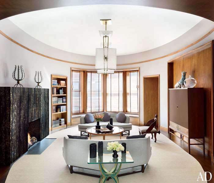 LIBRARY In the library, André Dubreuil lanterns top the mantel; the ceiling fixtures are 1960s Seguso, the Edward Wormley sofas are covered in a Larsen fabric, and the pillows are made of a Donghia textile.