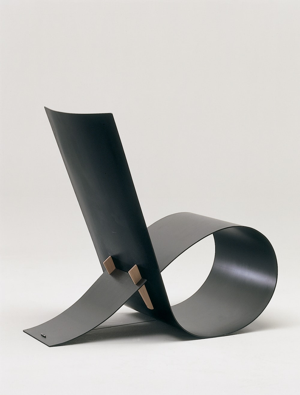 The sleek lines of the 1997 Loop chair by Niels Hvass are created in aluminum with wood details.