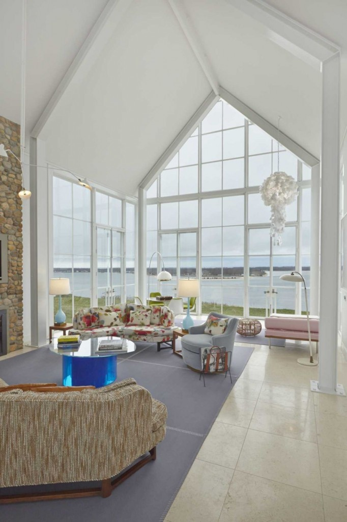 The living room addition in this Shelter Island residence was designed with a high peaked roof and walls of windows positioned to take full advantage of bay views. The home features two Edward Wormley corner sofas for Dunbar, of similar shape but slightly different proportions. Swivel chairs, also by Wormley, are covered in light-blue velvet and are arranged around a coffee table in the shape of an eye designed by Nicola L. (Credit: Courtesy of The Monacelli Press / Anastassios Mentis)
