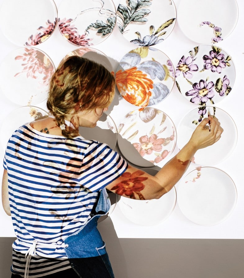 Hatch digitally projects her own designs onto the wall and traces them onto her plates.