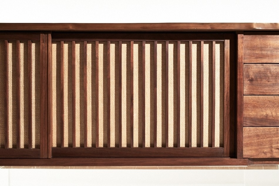 The backing behind the grills of the sliding walnut doors on the console's right side is made from woven pandanus cloth, which is sourced from the tropical pandan tree, also known as a screw pine or screw palm.