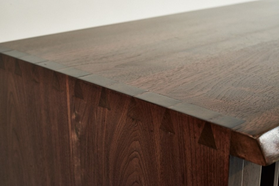 The console is made of Nakashima's favorite wood, American black walnut. Though its top and sides appear to be made from single slabs of wood, in fact it's comprised of different pieces meticulously fitted and glued together.